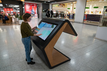 Woman with phone uses self-service kiosk in the shopping mall