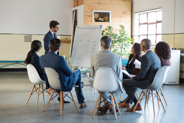 Confident business consultant working with employees. Group of workers sitting on chairs and listening speaker. Business meeting concept