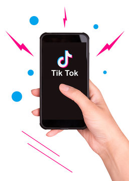Tik Tok application icon on smartphone screen close-up. The girl is holding a smartphone that shows the logo of the Tik Tok application. Tiktok Social network.