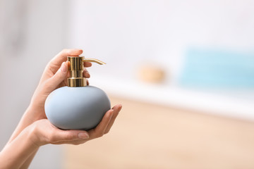Woman holding soap dispenser on blurred background, closeup. Space for text