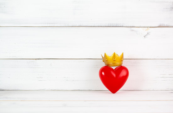 Red Heart Shaped with Golden Crown over white wood background. Symbol for queens or kings of lover , health concept with copy space.