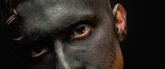 The dirty face of a working miner. Close-up portrait of a black face in soot. Stock photo.
