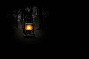 Vintage kerosene oil lantern lamp burning with a soft glow light in an dark forest / wood. Light in the darkness. Blurred background image of a glowing lantern against dark night time. Old lamp.