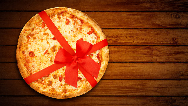 Holiday Pizza margherita with red ribbon bow for gift design on rustic dark brown background. Top View. Flat lay