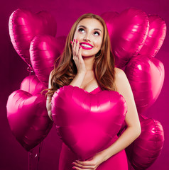 Pretty young woman with makeup and long ginger hair holding pink heart balloon on pink card backgroud