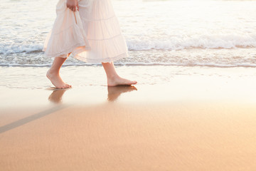 Beautiful woman walk on the beach with sea surf at sunset