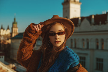 Outdoor close up fashion portrait of elegant fashionable woman wearing hat, trendy sunglasses, blue sweater, brown faux fur coat, posing in European city. Copy empty space for text Wall mural