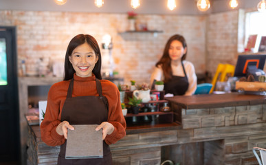 Young Asian female waitress wear apron and showing menu to customer business owner food and drink...