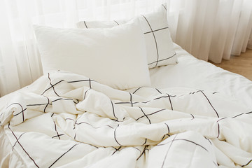 White bedding sheets with striped blanket and pillow. Messy bed.