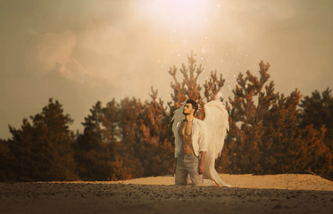 Young man fallen angel sad disappointed sinner sitting on knees in desert praying repentance. God's light blessing poured on man from heaven into desert on face of handsome guy in white clothes wings