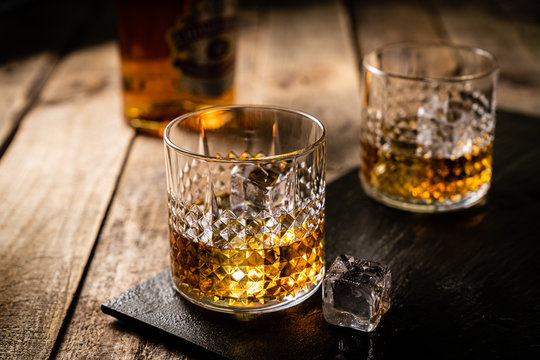 Whiskey in glasses on wood background, copy space, toned