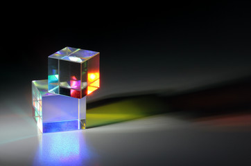 Two bright luminous prism cubes refract light in different colors
