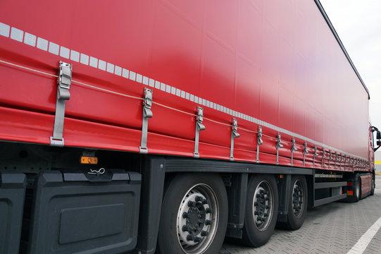 Red tarpaulin covering the semi-trailer of the trucks. Truck transport.