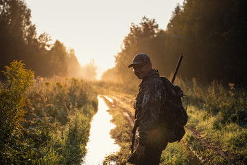 Summer hunting at sunrise. Hunter moving With Shotgun and Looking For Prey. Wall mural