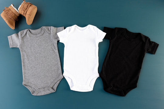Three baby bodysuits on a blue background with baby shoes mockup - 3 baby grows flat lay (white, grey & black)