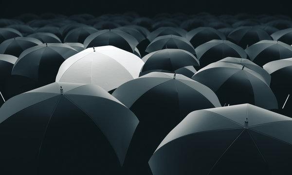 White umbrella in mass of black umbrellas