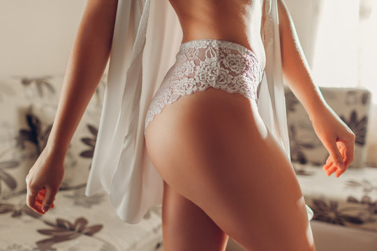 Slim woman wearing sexy lace underwear and dressing gown at home. White high-waist panties on sportive booty