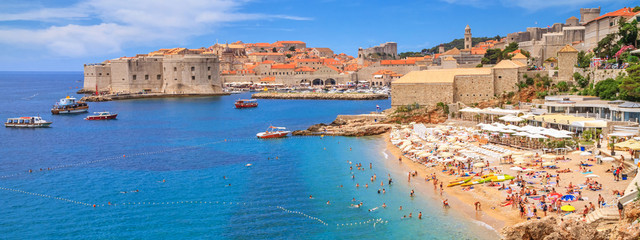 Coastal summer landscape - view of the city beach on the background of the Old Town of Dubrovnik on the Adriatic coast of Croatia