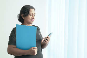 Smart and beautiful Indian corporate woman with a blue file standing by the office windows and looking at the phone.