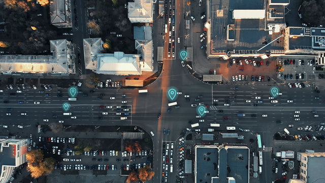 Aerial view of city intersection with many cars and GPS navigation system symbols. Autonomous driverless vehicles in city traffic. Future transportation concept.