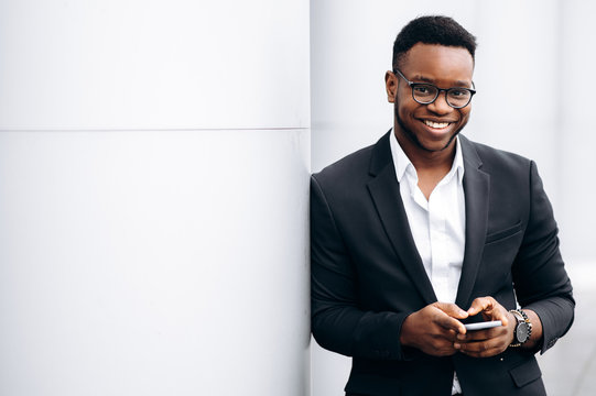 Attractive african american businessman in stylish suit is smiling with phone in his hands, outdoors
