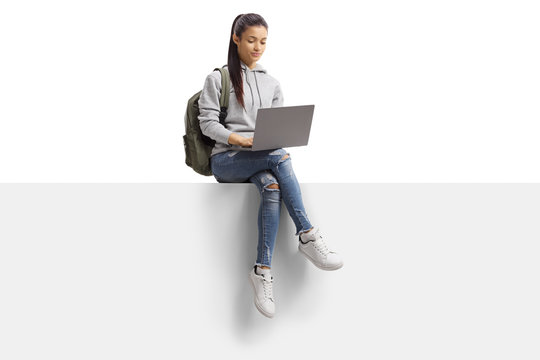 Female student sitting on a blank board and using a laptop computer