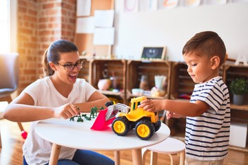 Beautiful teacher and toddler boy playing with tractor and cars at kindergarten