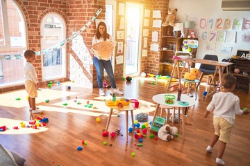 Beautiful teacher and toddlers playing basketball using balls and wicker basket  around lots of...