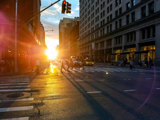 Fotomurales - Crowds of busy people walking across an intersection in Midtown Manhattan New York City with sunlight background