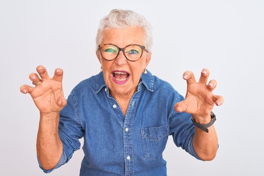 Senior grey-haired woman wearing denim shirt and glasses over isolated white background smiling funny doing claw gesture as cat, aggressive and sexy expression