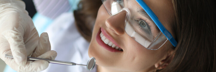 Young smiling beauty woman in dentinst office portrait. Prevention of toothache and tooth decay concept.