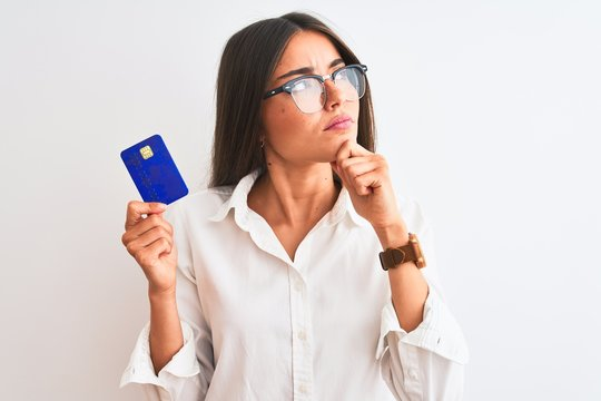 Young businesswoman wearing glasses holding credit card over isolated white background serious face thinking about question, very confused idea