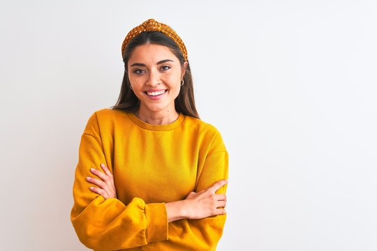 Young beautiful woman wearing yellow sweater and diadem over isolated white background happy face smiling with crossed arms looking at the camera. Positive person.