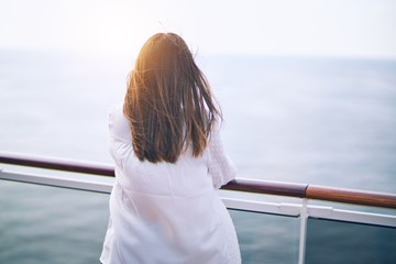 Young beautiful woman on vacation standing on a deck of ship with smile on face backwards doing a...