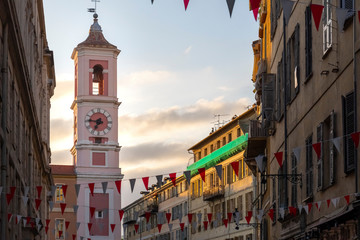 In de dag Nice Evening view of the Rusca Palace Clock Tower at the Place du Palais du Justice with red and white flags draped over the street in Nice, France