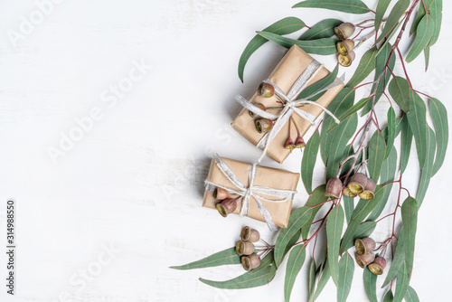 Gifts surrounded by Australian native eucalyptus leaves and gum nuts tied with silver ribbon, on a white background. Celebration can be Birthday, Anniversary, Christmas, Valentines day or mothers day.