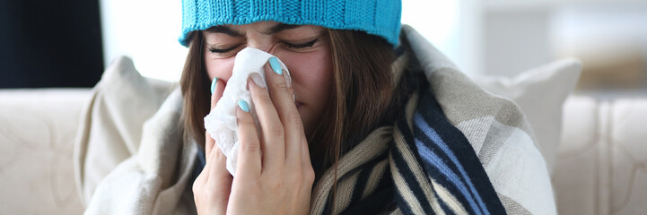 Portrait of beautiful woman blowing into white tissue and closing cute eyes. Poor girl sitting indoors wearing warm clothes and sneezing from severe flu. Hard virus concept