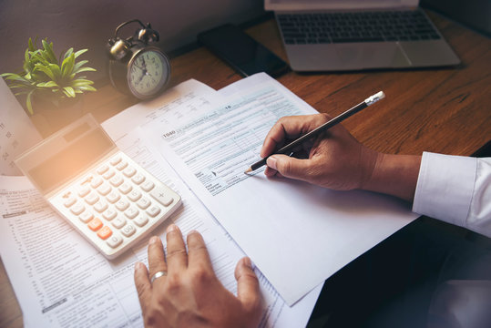 Budget planning concept, Accountant is calculating company's annual tax. Calendar 2020 and personal income tax forms for those who have income under US law placed on office desk.