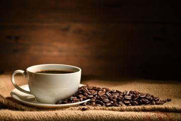 Cup of coffee and coffee beans on burlap sack on old wooden background