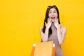 Young Asian woman carrying colorful shopping bags in surprised and excited gesture