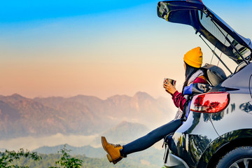 Aluminium Prints Salmon Woman traveller enjoy coffee time on back storage of car with scenery view of the mountain and mist morning in background