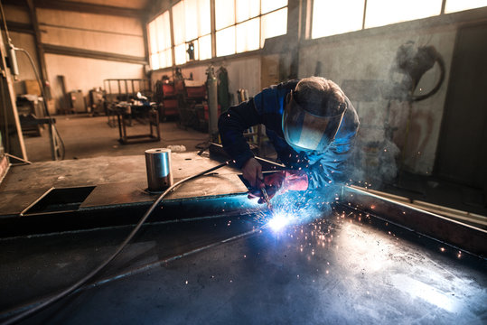 Professional welder welding metal construction parts in industrial workshop. An experienced worker joining iron parts using MIG welding technique.