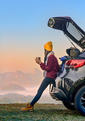 Woman traveller enjoy coffee time on back storage of car with scenery view of the mountain and mist...