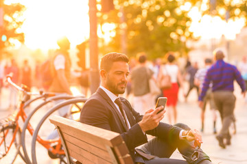 A businessmen sitting on a bench and using his smartphone