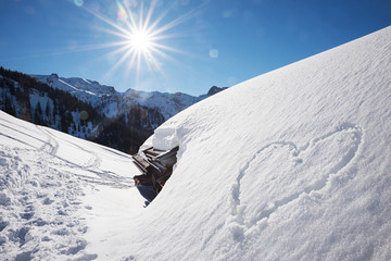 bright sunny winter landscape tirol, snow covered alp hut and love heart