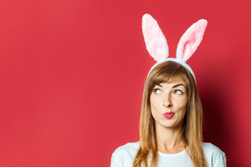 Young beautiful woman with rabbit ears on a pink background. Easter concept