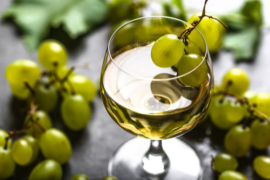 White wine glass and fresh grapes
