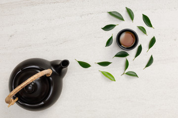 Photo sur Aluminium The Cup of hot tea with teapot, green tea leaves and dried herbs top view on the white stone table empty space, Organic product from the nature for healthy with traditional style