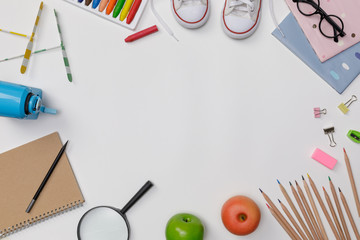 Creative flatlay of education white table with student books, shoes, colorful crayon, eye glasses,...