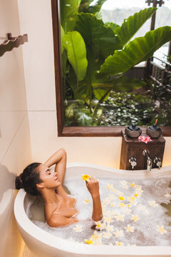 Asian woman enjoying in flower spa bath with foam, bubbles and yellow frangipani flowers. Relaxing Spa wellness treatment. Tropical garden view in window